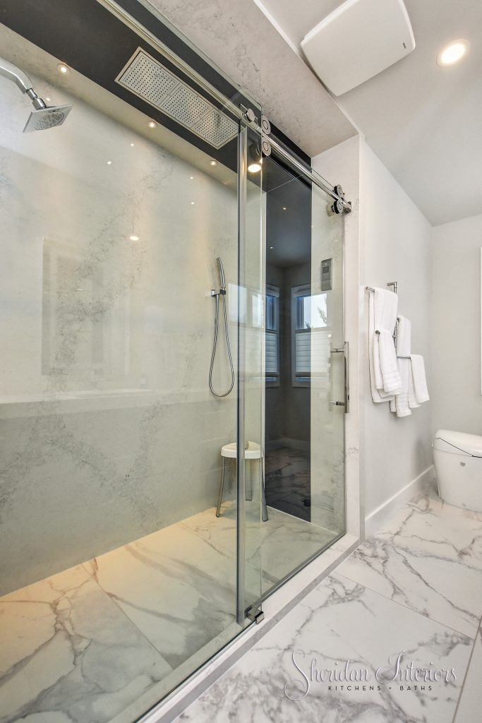 contemporary bathroom with roll in shower and large format porcelain tiles on floor. Quartz panels for shower walls interior designer ottawa interior designer cornwall
